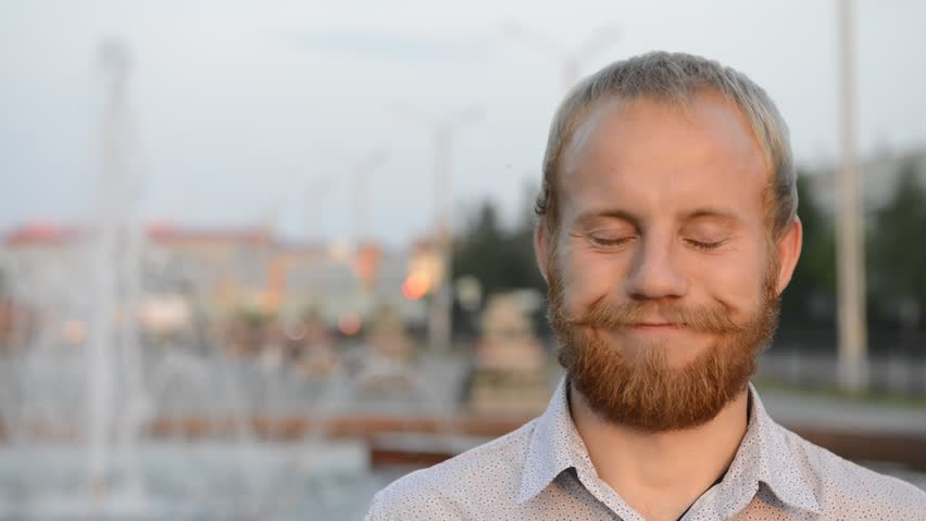 Blond man with blue eyes and beard near the fountain looking at the camera | Shutterstock HD Video #17886394