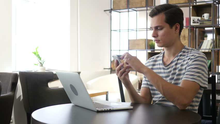 Young man using smart phone and notebook | Shutterstock HD Video #17914138