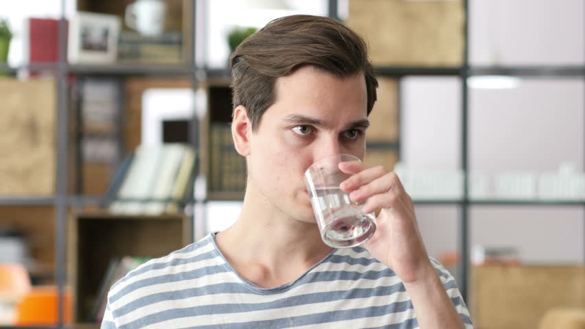 Handsome businessman in casual cloth drinking water in office | Shutterstock HD Video #17914201