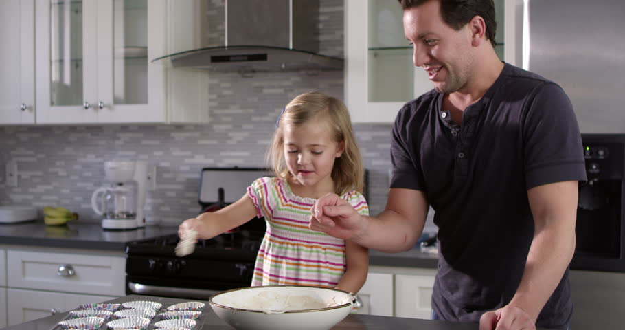 Caucasian girl spooning out cake mix mix for baking with her dad, shot on R3D | Shutterstock HD Video #17914579