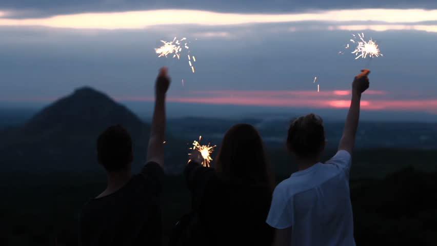Friends at sunset in the mountains rejoice and waving sparklers.