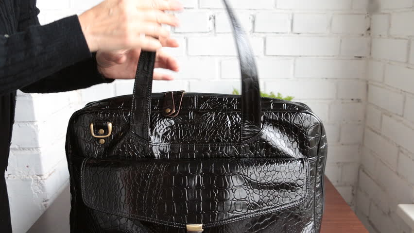 Woman taking out things from her black patent leather bag: laptop, wallet, scarf, etc Royalty-Free Stock Footage #17938330