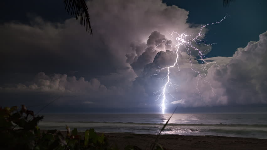 HD - Extreme lightning storm timelapse over the moonlit Florida ocean at night.