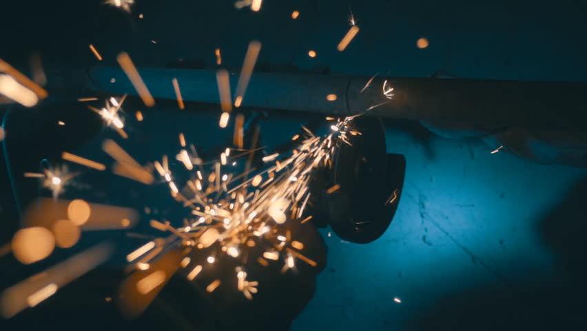 The angular grinding machine is cutting the pipe on a blue background and a lot of sparks flying straight into the camera. Slow motion, high speed camera, 250fps