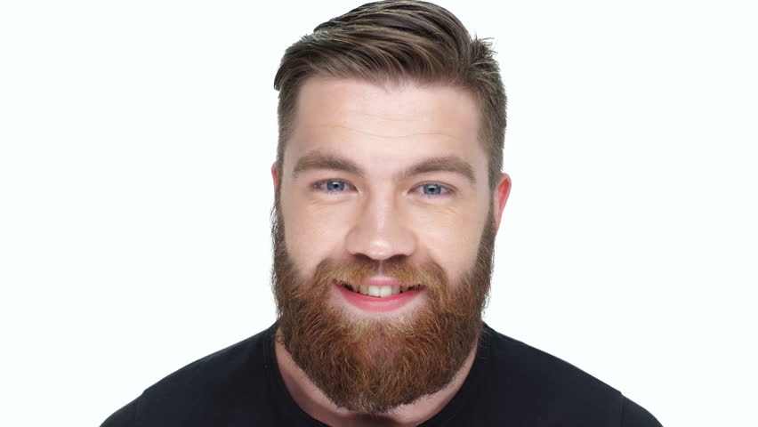 Smiling young bearded man nods his head and looking at camera
