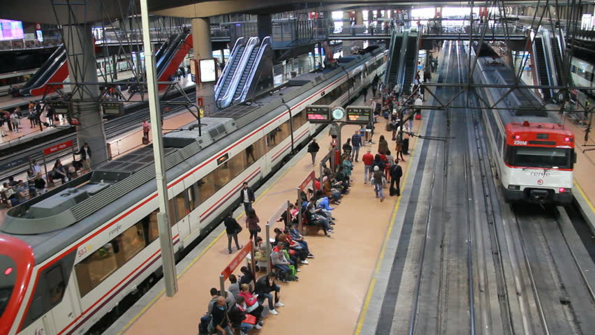MADRID, SPAIN - MAY 27, 2016: People walk on platform with riding trains in Atocha Railway Station on May 27, 2016 in Madrid, Spain. Atocha railway station is the central station of Madrid.   Shutterstock HD Video #17975491