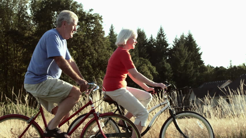 Senior couple enjoy time together bike riding. Wide shot, in real time   Shutterstock HD Video #17981164
