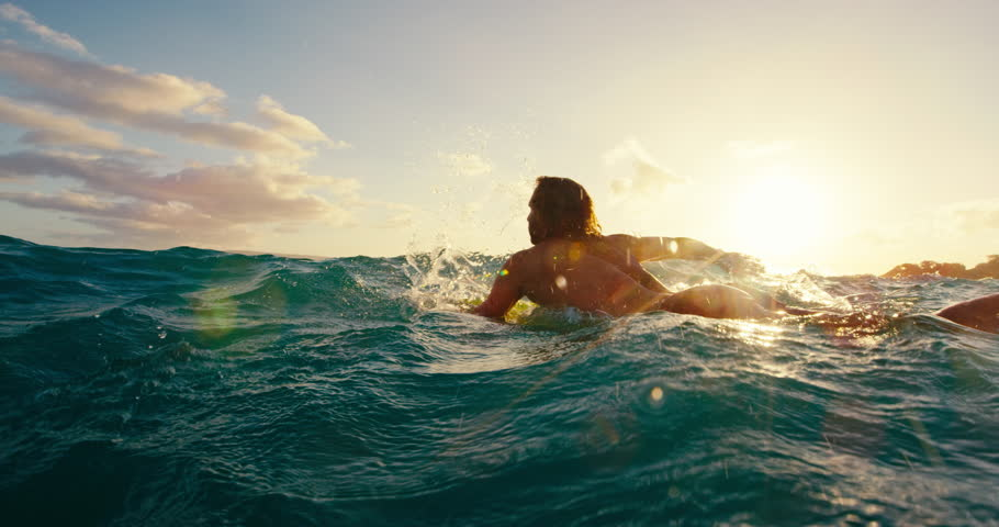 Surfer paddling over blue ocean wave at sunset in slow motion, outdoor fitness lifestyle | Shutterstock HD Video #17997595