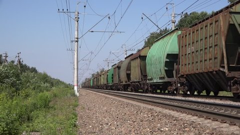 Mga - Gory track section, Saint Petersburg Region, Russia - 2 July 2016. Triple-section powerful electric locomotive hauls a hopper wagon train bound to St. Peterburg