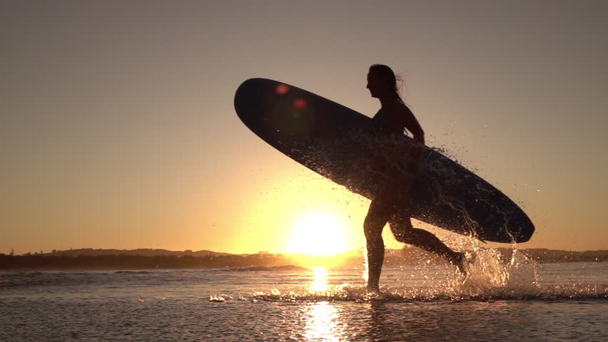 SLOW MOTION SILHOUETTE: Young surfer girl enjoying seaside summer vacation activities, holding longboard surfboard and running in shallow water in beautiful ocean at amazing golden light sunset #18000454