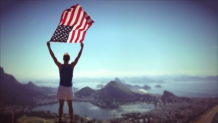 Athlete stands holding an American flag waving in slow motion at a bright overlook of the city skyline of Rio de Janeiro, Brazil