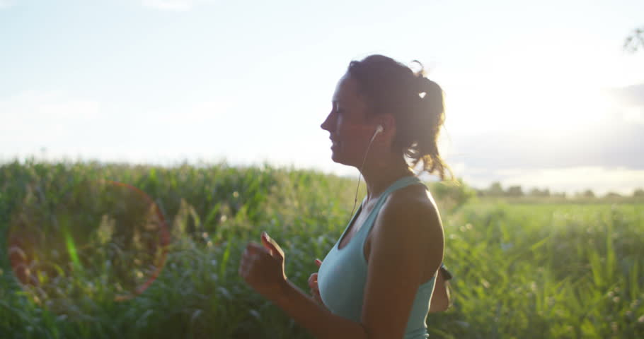 A happy girl fit relaxed jogging and running in a street with trees and nature, using headphones for music and run slow in sunset. concept of happiness for sports and fitness relaxation in nature.sun   Shutterstock HD Video #18013198