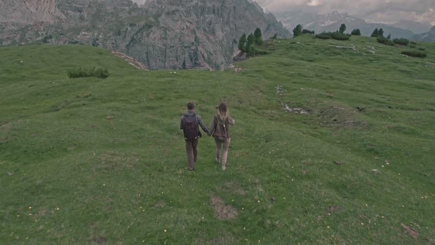 Drone flying over a couple who walks on the field in Tre Cime di Lavaredo, Italia. #18014029