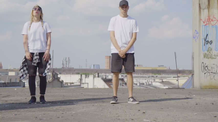 Video of active young couple dancing hip hop on the rooftop with city background behind.