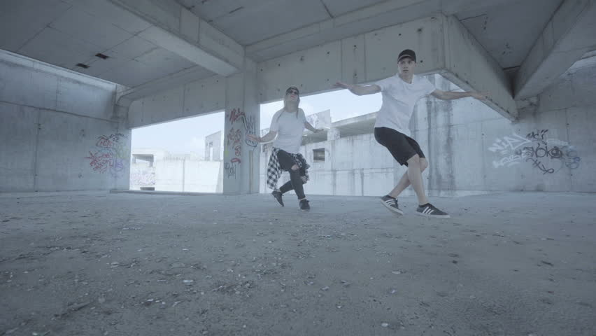 Video of active young couple dancing hip hop choreography and breaking the floor in an abandoned carpark building.