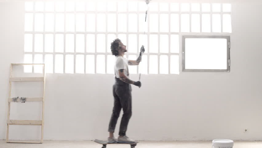 Funny curly man wears pants with suspenders skates with paint bucket from one side to other and falls in the end, small comedy about home renovation #18026449