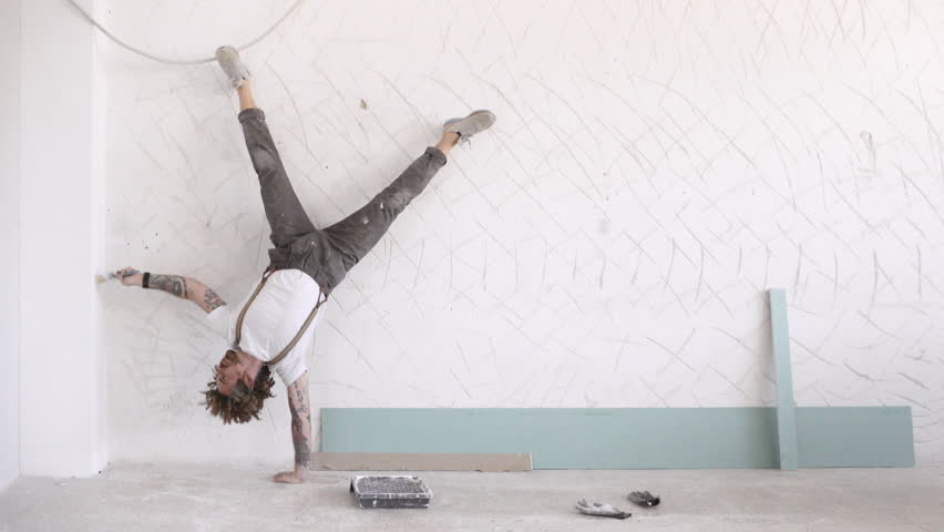 Funny curly man wears pants with suspenders makes sport exercises white painting wall, one hand headstand #18026467