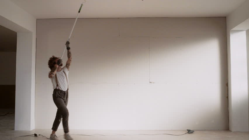 Funny curly man wears pants with suspenders acts like he is dancing waltz while painting celling with brush roller and white paint Home diy renovation #18026470