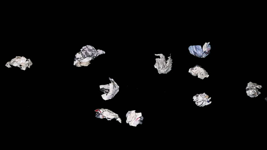 Paper rubbish and garbage cast against black background. Time lapse.