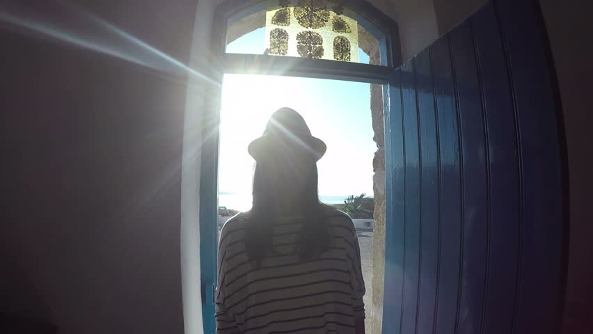 Silhouette of a girl. Silhouette of girl in hat, which is on the way out of the building.The glare of sunlight on the girl.   Shutterstock HD Video #18032050
