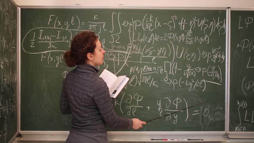 Woman with book and pointer looking to blackboard and to book. | Shutterstock HD Video #18056191