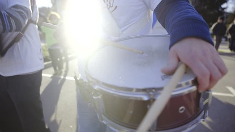Playing drums at carnival closeup 4K. Group of people playing music as band at carnival. Drumsticks hitting on drums.