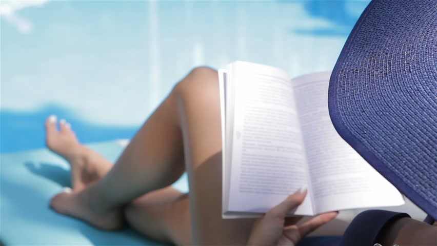 Close up of young caucasian woman turning the page of the book near the swimming pool. Slim girl touching the pages of the book by her fingers. Tanned woman lying with bended knee