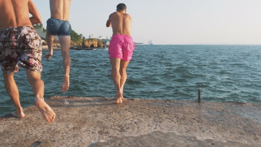 Group of friends running and jumping off sea pier in the water, slow motion