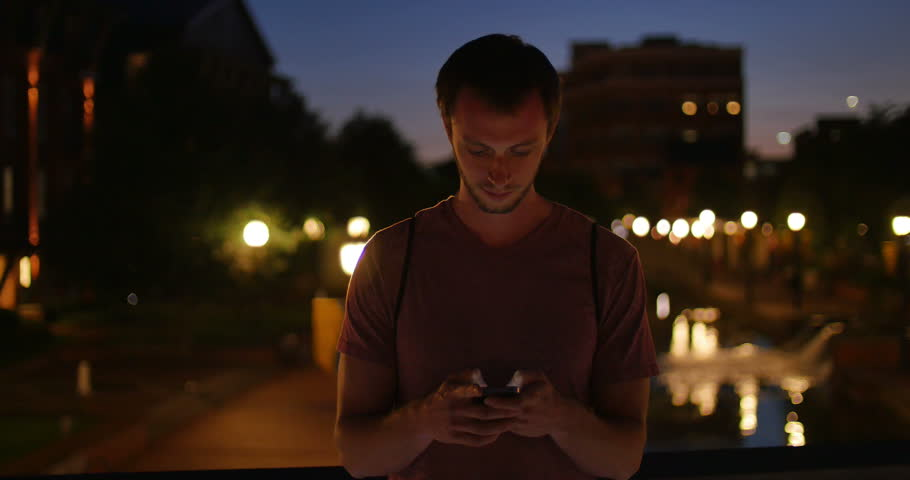Young Man on Smart Phone Looks Up and Smiles City Lights Night, 4K   Shutterstock HD Video #18077575