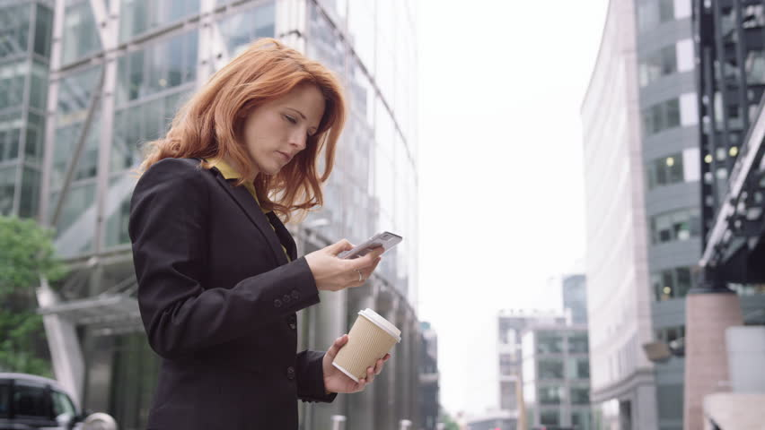 Businesswoman in city using smart phone with takeaway coffee | Shutterstock HD Video #18087421