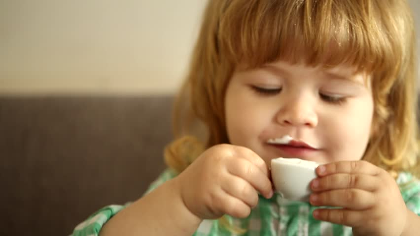 little cute baby drinking milk from a toy cup of coffee