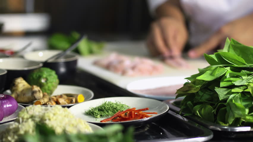 Close-up of chef hands cooking and preparing Asian food and sushi in restaurant kitchen. Rack focus