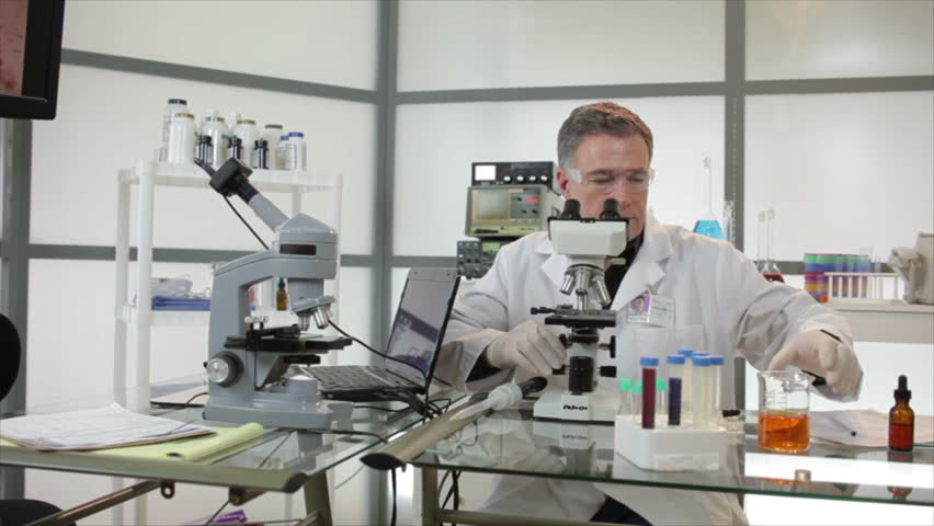 A woman and man who appear to be scientists or chemists working in a laboratory using microscopes and other technologies.