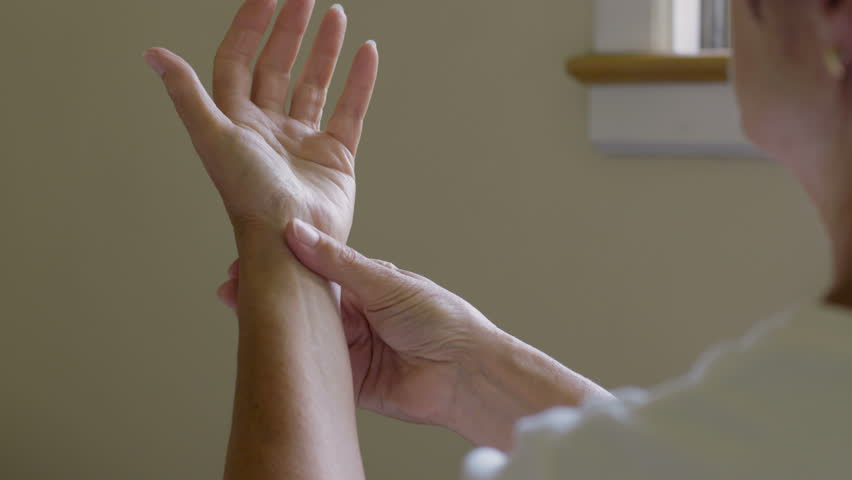 Woman massaging her arthritic hand and wrist