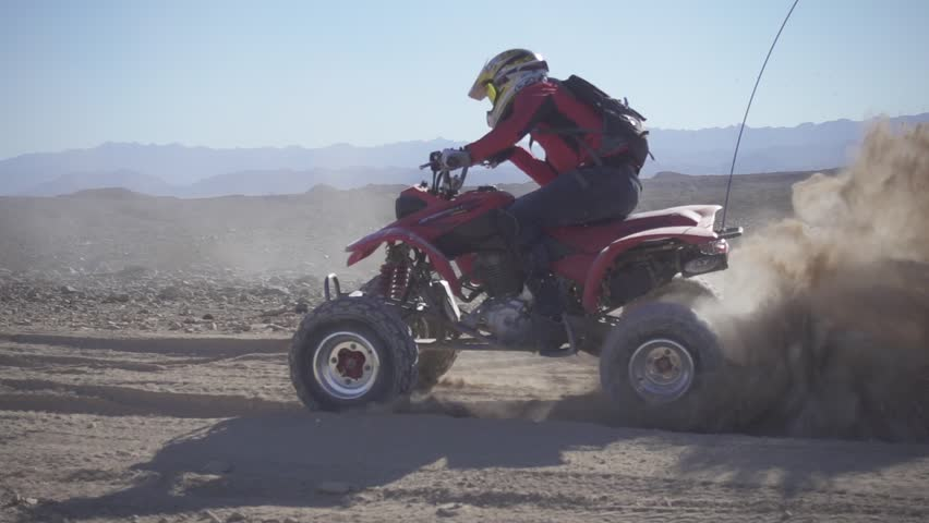 Slow motion shot of quad with extreme sand ejection