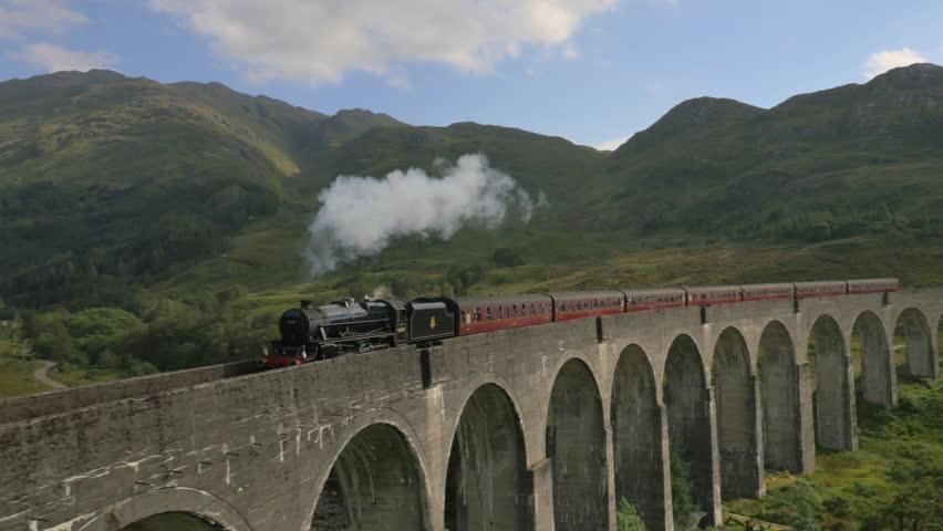Aerial view of Steam Train crossing Glenfinnan Viaduct Scotland