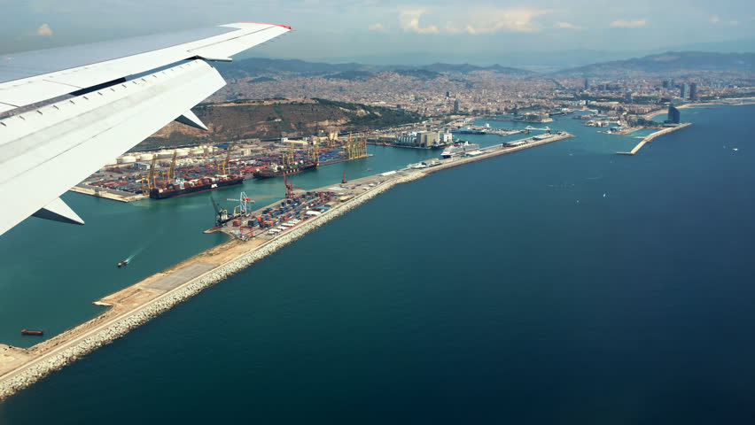 Landing in Barcelona, Spain, Catalonia. Traveling by air. Bird's-eye view through an airplane window. Flying aerial over the Barcelona city port, houses and streets. A wing is seen in left top corner.