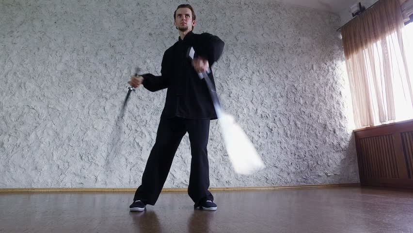 Man practicing elements of tai chi. A man rotating steel swords around a body 4K | Shutterstock HD Video #18163921