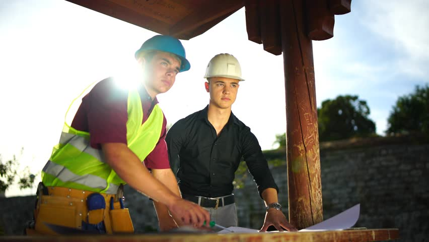 Construction engineer and manager are discussing over the plans of a building. #18168079