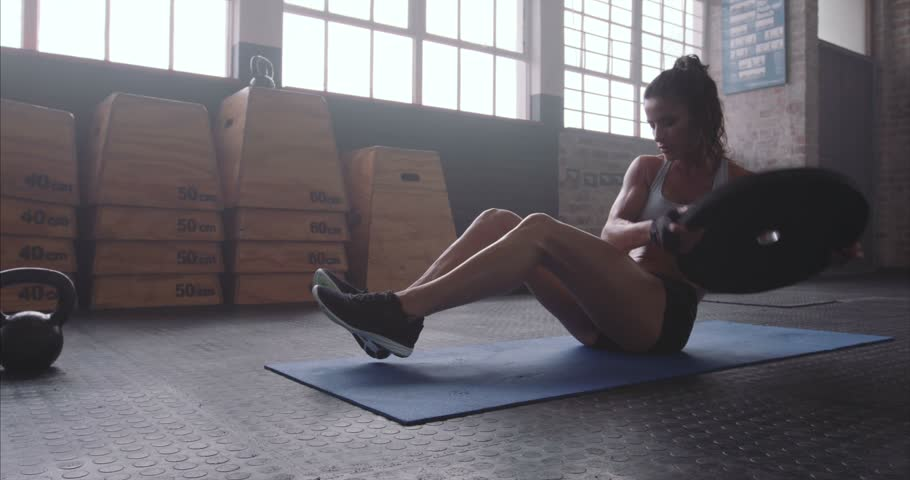 Muscular woman exercising with a weight plate. Fitness woman working out on core muscles at cross fit gym. Weight plate torso twist on exercise mat.  | Shutterstock HD Video #18174223