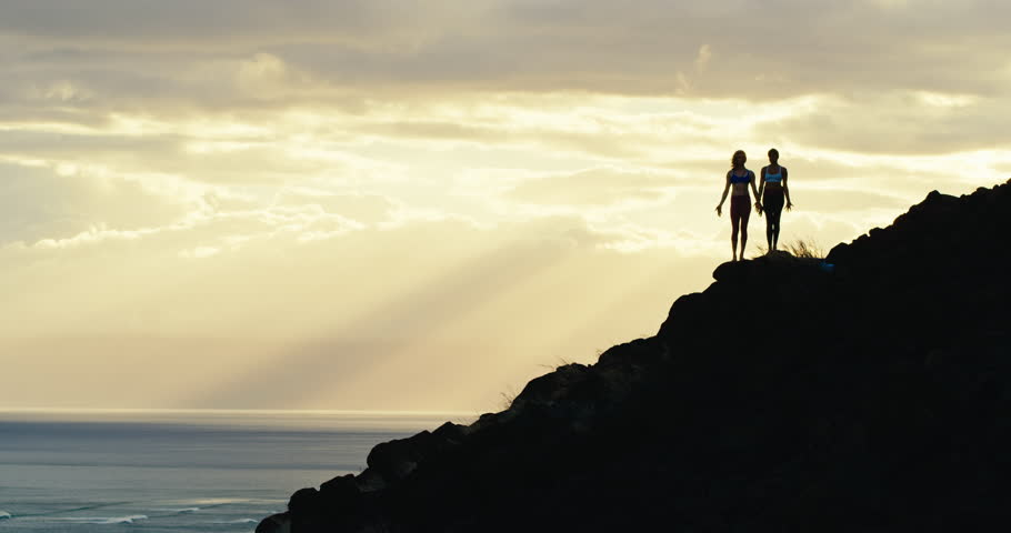 Yoga silhouette of two women at sunset in amazing natural landscape