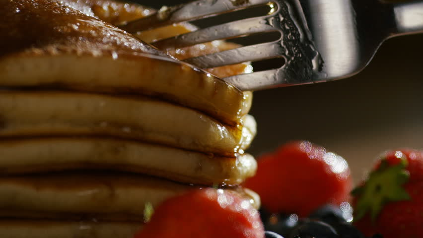 4K Fork taking a slice of stacked buttermilk pancakes drenched in maple syrup, in slow motion #18205705