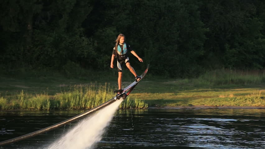 Young girl on the Hover board on the river, water jet spray.Young girl on the flying board flies over the lake water.Fly board rider. #18238960
