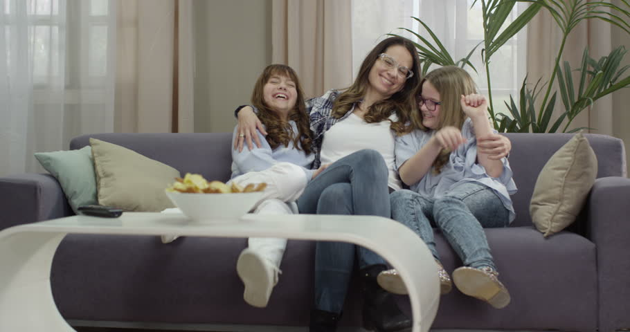 Mother and daughters hugging and smiling on sofa in the living room.