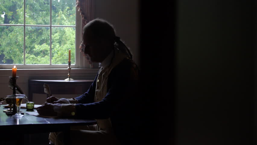 VIRGINIA - OCTOBER 2014 - Reenactment, President, founding father, Revolutionary War anniversary recreation -- Tabletop, quill writing, dipping ink and writing by candle light & by window, standing #18252205
