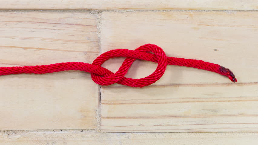 4K stop motion figure eight knot made from red synthetic rope, tightening on wooden background #18272089