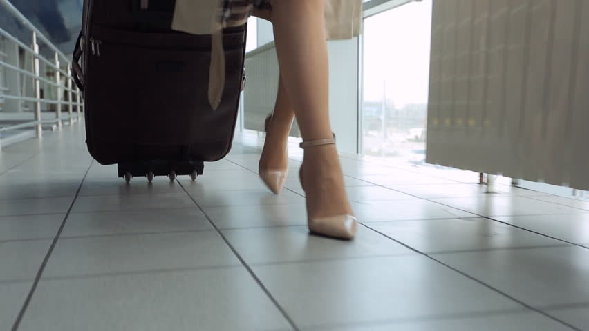 Woman in heels goes at airport and roll suitcase on wheels.
