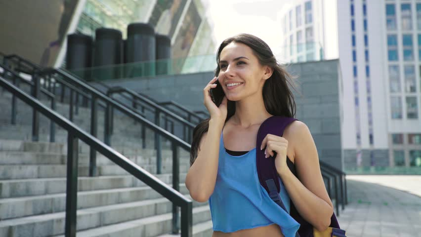 Charming brunette girl in sportswear and with sports bag talking on mobile phone, walking after training internet, modern, headphones, sunset, tracker, outside, looking, smiling, sporty, morning  #18280630