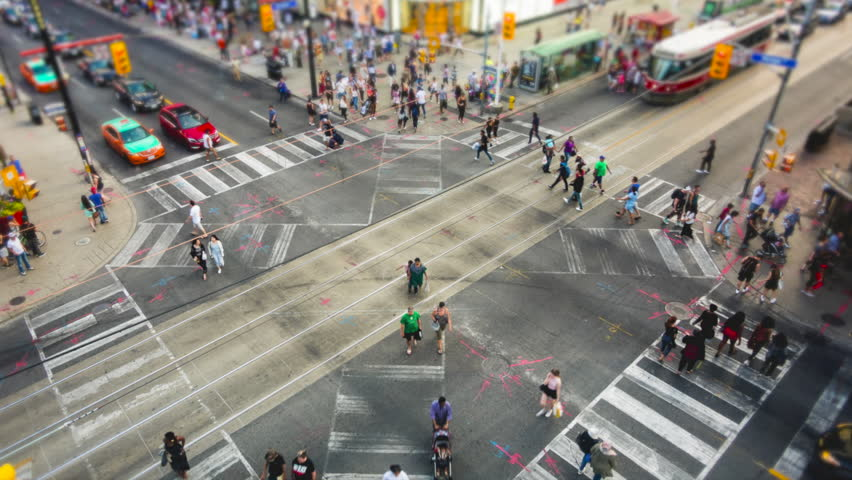 Toronto, Canada, time lapse view of people and traffic crossing busy intersection at Yonge-Dundas Square.