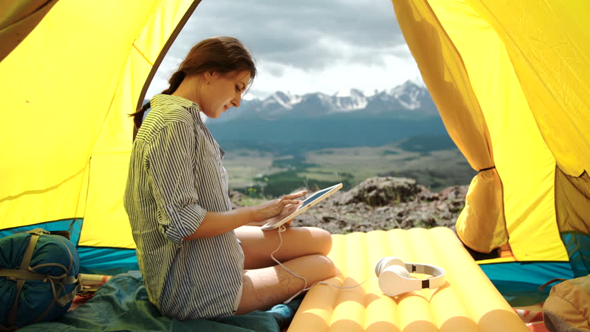Woman smiling and using a tablet on a tent #18296908